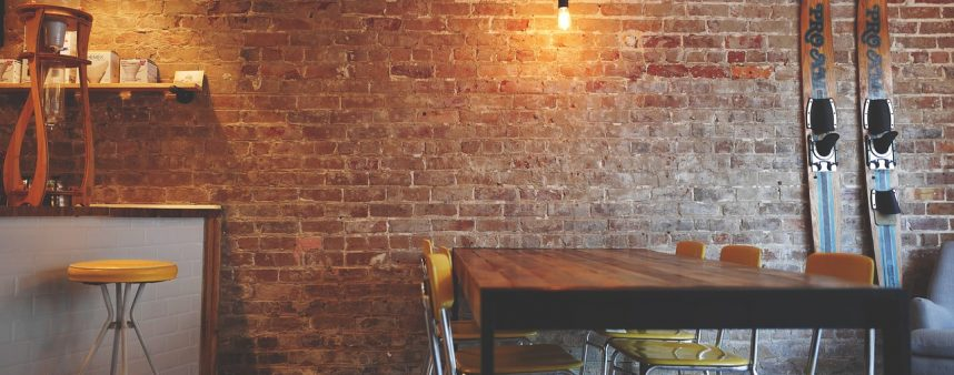 A picture of a restaurant featuring exposed bricks walls, a bar with a bright yellow stool, wood restaurant tables with yellow chairs, and come decorative skis propped against the wall.