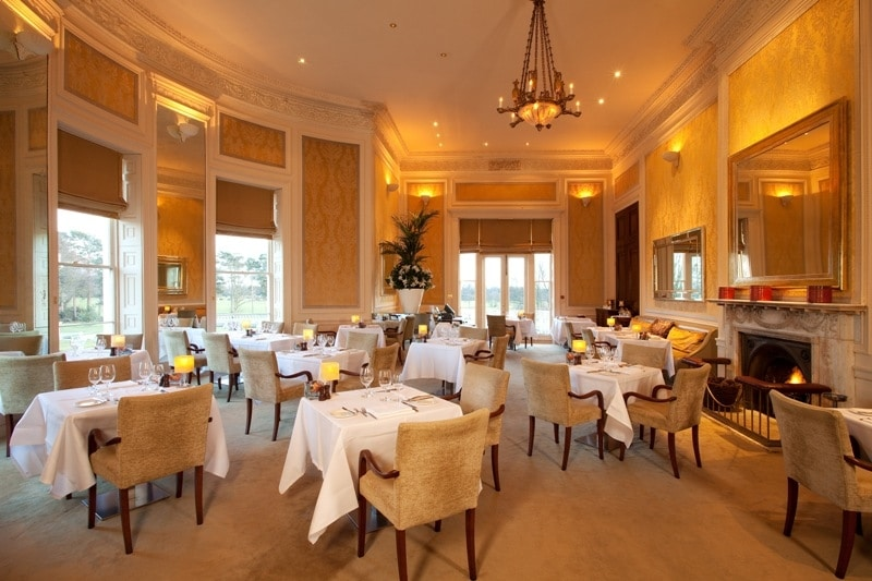 A photo of a fine dining restaurant room, with cosy upholstered restaurant chairs and restaurant tables spaced generously apart to create an ambient feel.